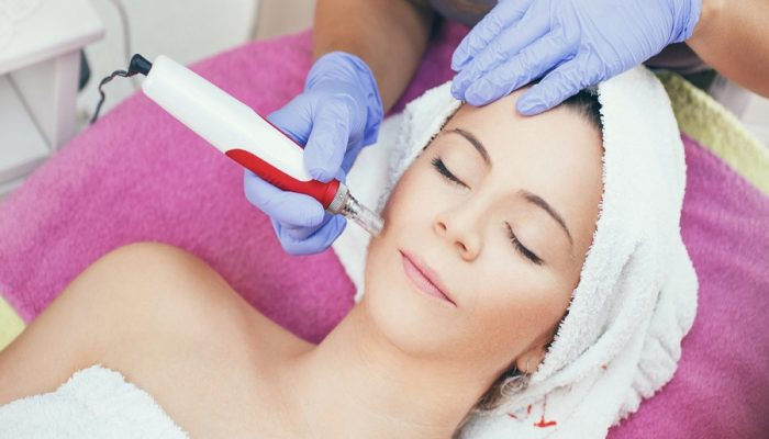 Mid 30's woman having mesotherapy facial treatment at beauty salon. It's being done by professional female beautician. The client is resting on massage table wrapped in white towel. Top view.