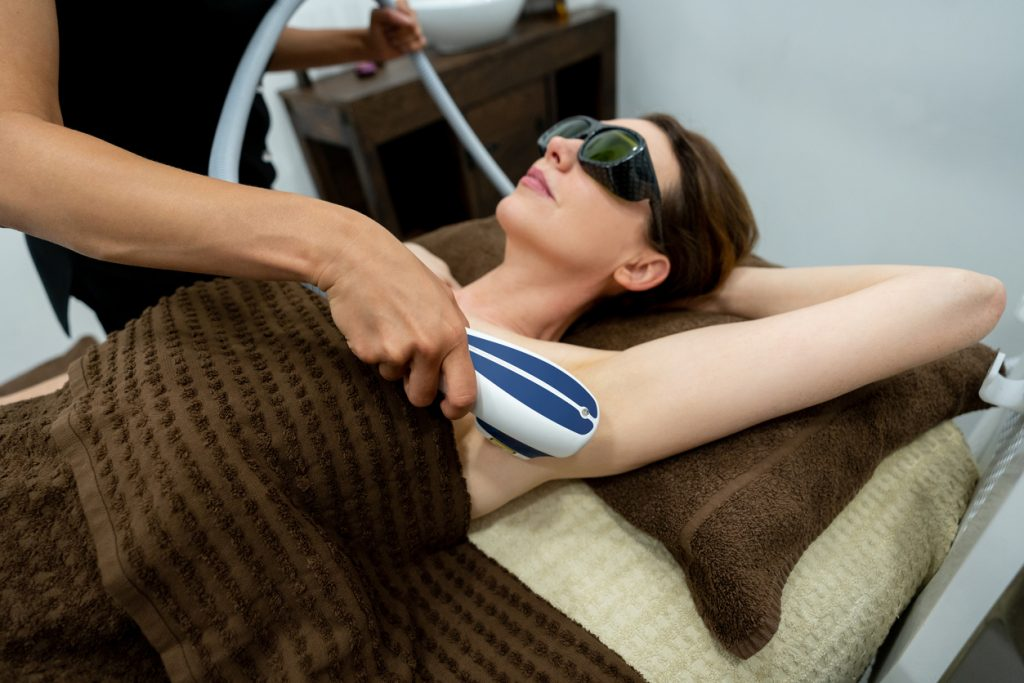 Woman at the spa getting a hair removal laser treatment in her armpits
