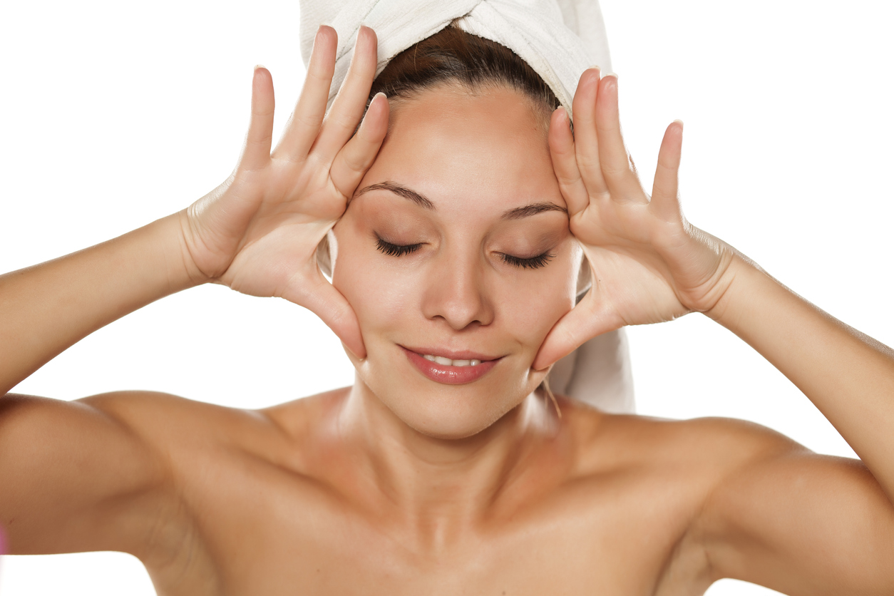 young beautiful woman tightens her face with her hands