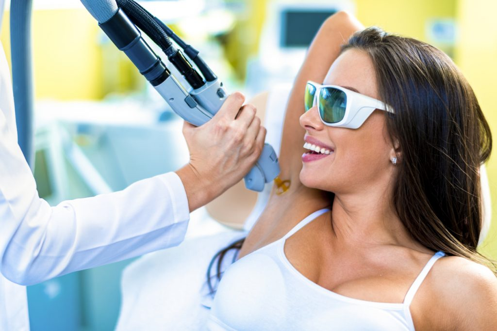 A woman getting her hair removed from armpit are by a laser treatment in a beauty salon