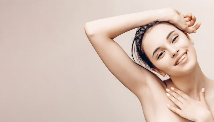 Natural beauty portrait of female face and body with perfect skin. Deodorant advertising and hair epilation concept
