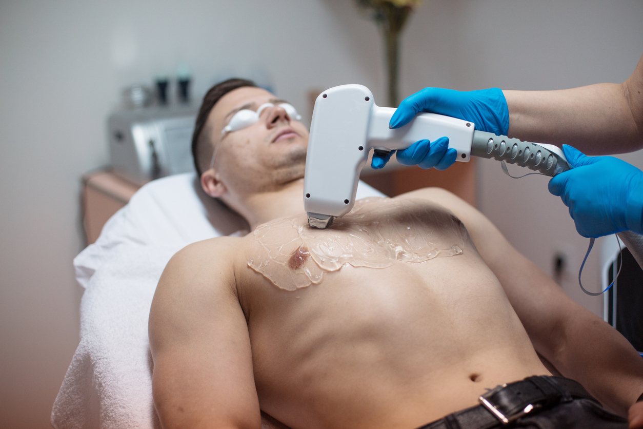Beautician removing chest hair with laser epilator